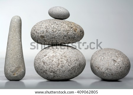 Stack of stones - pebbles on grey background - stock photo