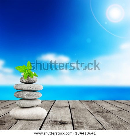 Stack of stones with mint leaf on wood planks with view on beauty sea under blue clouds sky. Alternative medicine concept - stock photo