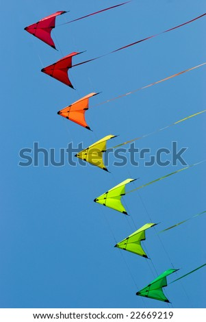 Stack of stunt kites in rainbow colours on a blue sky background - stock photo