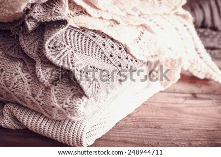 stack of sweaters on a wooden background. vintage toning