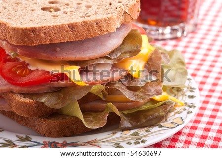 stack  of tasty sandwiches on a plate and a glass of drink