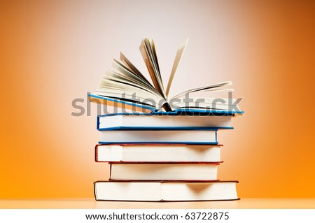 Stack of text books against gradient background - stock photo