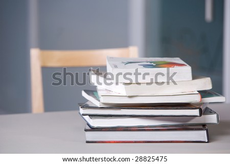 Stack of textbooks on a desk in a modern classroom - stock photo