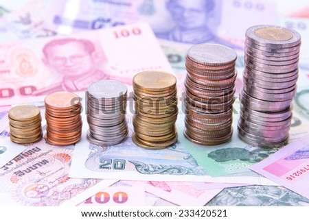 Stack of Thai coins on bank notes money background - stock photo
