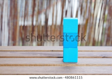 Stack of three blue square wooden toy blocks on table