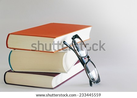 stack of three books with reading glasses leaning against the side, gray background, copy space - stock photo