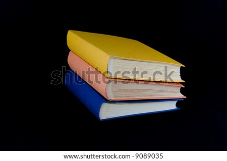 Stack of three books,with yellow, orange, and blue covers. Isolated against black background. - stock photo