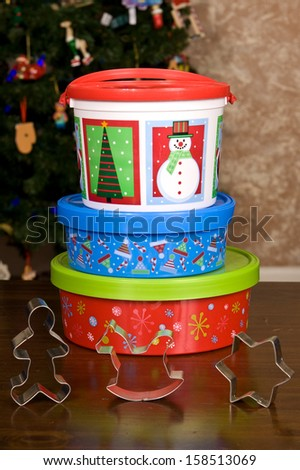 Stack of three Christmas Holiday Cookie Containers and cookie cutters sitting on a wooden table top in front of a Christmas tree. - stock photo