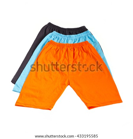 Stack of three colors kid pants isolated on white background