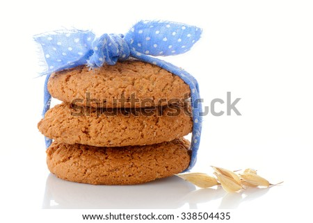 Stack of three homemade oatmeal cookies tied with blue ribbon in small white polka dots and ear of oats, isolated on white background