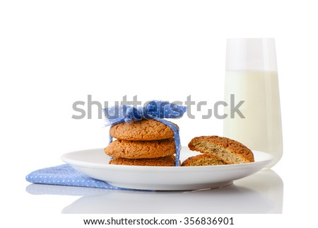 Stack of three homemade oatmeal cookies tied with blue ribbon in small white polka dots and halves of cookies on white ceramic plate on blue napkin and glass of milk, isolated on white background - stock photo