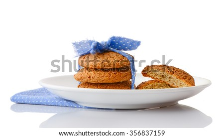 Stack of three homemade oatmeal cookies tied with blue ribbon in small white polka dots and halves of cookies on white ceramic plate on matching blue napkin, isolated on white background - stock photo