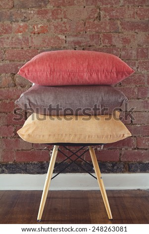 Stack of three linen cushions on chair brick wall background - stock photo