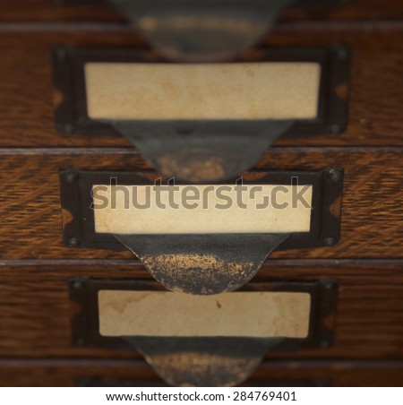 Stack of three old, oak flat file drawers with blank yellowed tags in tarnished brass label holders. Shallow DOF with focus and lighting on the middle drawer.   - stock photo