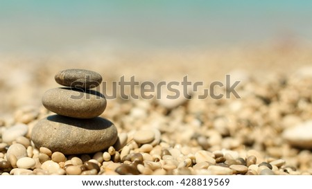 Stack of three rocks on a pebble sea beach. Zen stones. Meditation.