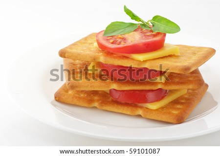 Stack of three square crackers with slices of cheese, tomato and basil in white plate on white background. - stock photo