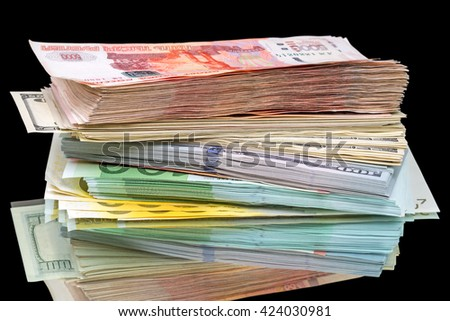 Stack of three types of currencies (dollars, euros, rubles) on a black background - stock photo