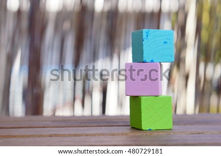 Stack of three wooden toy cubes on table