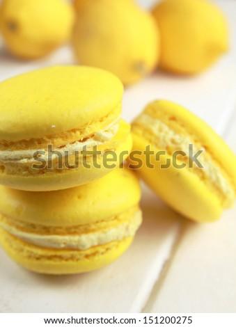 Stack of three yellow lemon macaron with lemon in background - stock photo