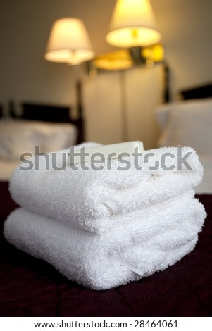 stack of towels and soap on a hotel bed - stock photo