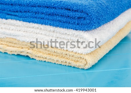 Stack of towels on a blue wooden background.