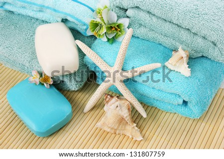 Stack of towels, soaps, starfish, shells on mat background. - stock photo