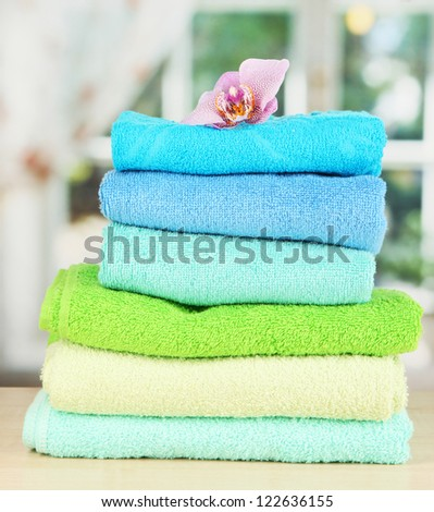 Stack of towels with fragrant flower on window background - stock photo
