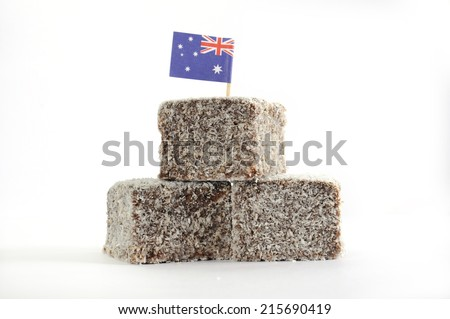 Stack of traditional Australian cake slice, Lamington squares, with chocolate icing and coconut with Australian flag on white background. - stock photo