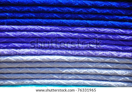 Stack of traditional woven alpaca blankets in different shades of blue - stock photo