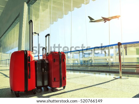 stack of traveling luggage in airport terminal and passenger plane flying over sky