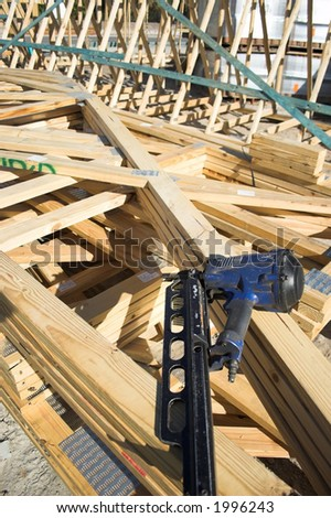 Stack of trusses , with frame gun on top, (focus on the nailgun) - stock photo