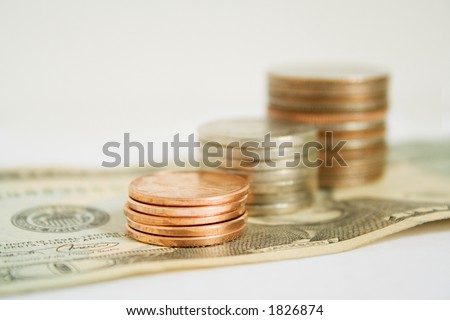 Stack of US coins on top of a US twenty dollar bill. - stock photo
