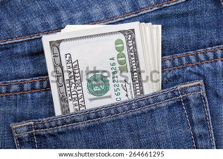 Stack of US dollars sticking out of his jeans pocket - stock photo