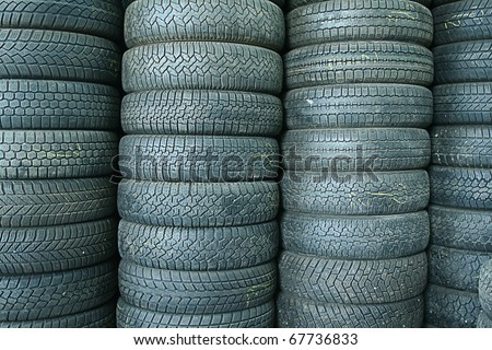 Stack of used tires in a junkyard - stock photo