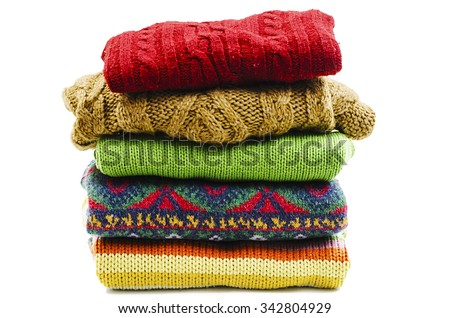 Stack of various sweaters. Winter style. Isolated on white background - stock photo