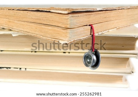 Stack of various used books with an original hand-made bookmark in the form of tea cup and saucer - stock photo