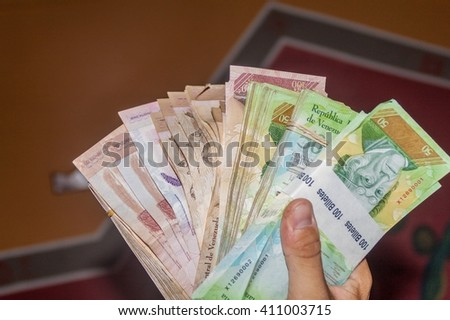 Stack of Venezuelan currency (Bolivar Fuerte) is hold in the hand. Due to hyperinflation, it is necessary to use thick stack of bills to cover basic needs. - stock photo