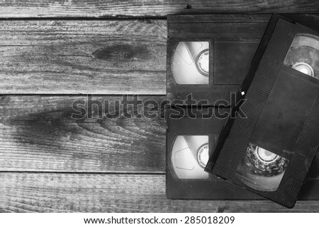 stack of VHS video tape cassette over wooden background. top view black and white photo - stock photo