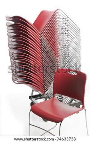 Stack of vibrant orange plastic chairs for a conference - stock photo