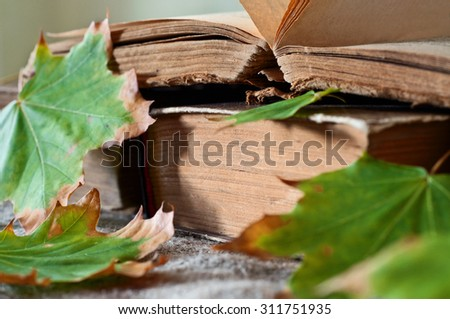 stack of vintage books in autumn maple leaves close up. Copy space. Free space for text - stock photo