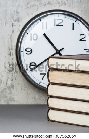 Stack of vintage books over the wall with clock - stock photo
