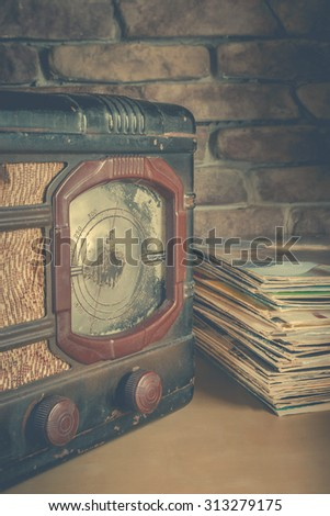 Stack of vinyl records and old players on the brick wall background