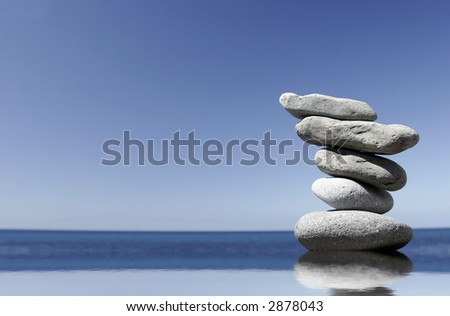 Stack of volcanic pebbles in calm water