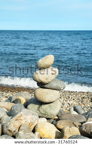 Stack of volcanic pebbles on beach - stock photo