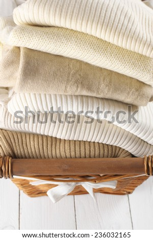 Stack of warm sweaters in basket on white wood. - stock photo