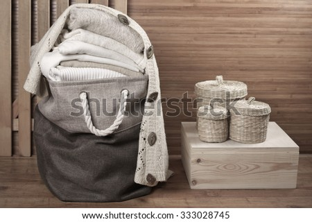 Stack of warm white knitwear in fabric basket in wooden bathroom. - stock photo