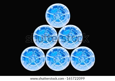 stack of water bottles on black background - stock photo