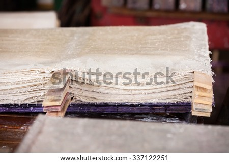 Stack of wet papers drying in factory - stock photo