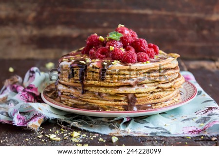 Stack of wheat golden pancakes or pancake cake with freshly picked raspberry, chopped pistachios, chocolate sauce on a dessert plate  - stock photo