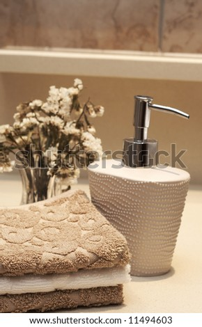Stack of white and brown towels and bottle of liquid soap with some dry flowers in the bathroom - stock photo